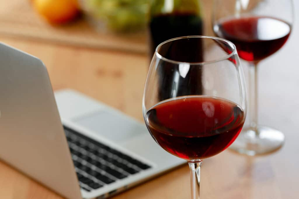Laptop and glass of red wine on wooden kitchen table close up