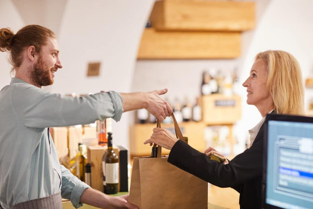 Side view portrait of contemporary man selling wine to woman in shop