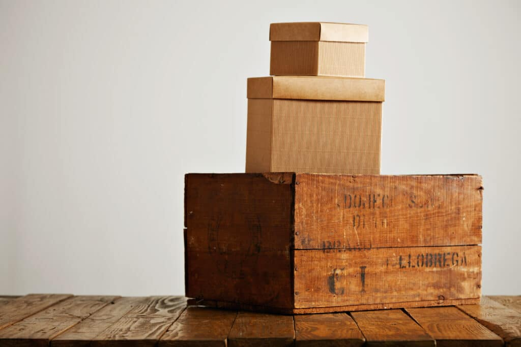 Different sized craft cardboard boxes with covers piled on top of a vintage wine crate isolated on white