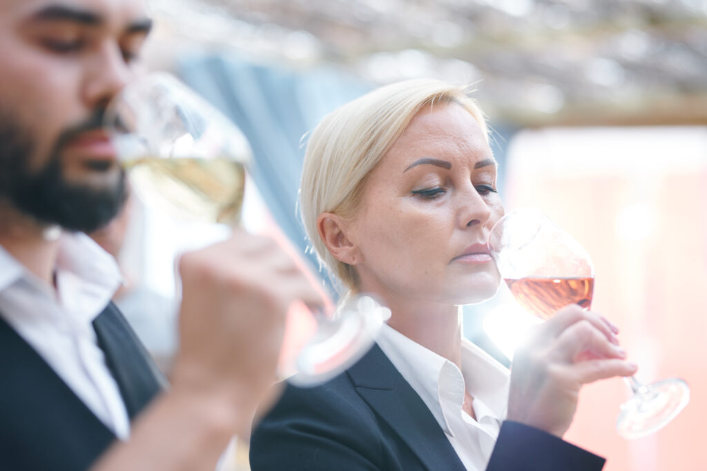 Blonde mature female sommelier smelling wine in wineglass