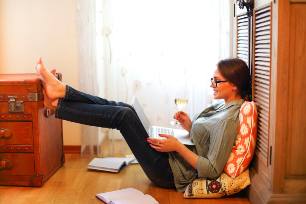 Young woman sitting on floor near glass of wine and open planner and browsing laptop while working on remote project at home
