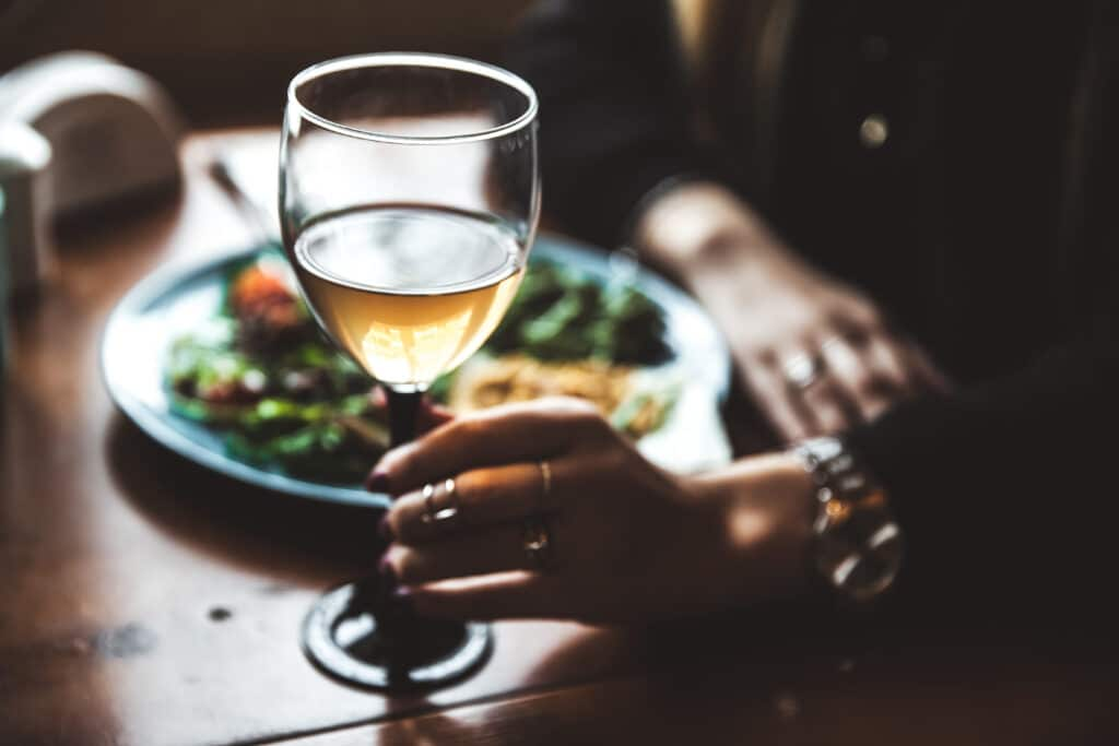 Female hand with glass of wine and food in the background