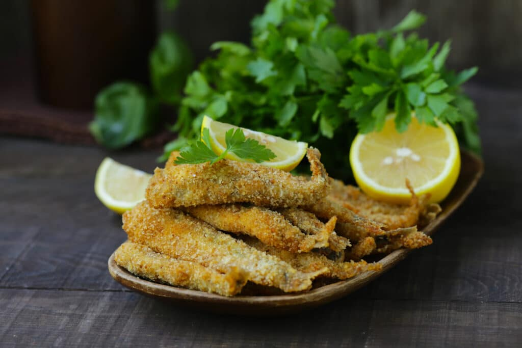 german fried fish for lunch, with lemon and herbs
