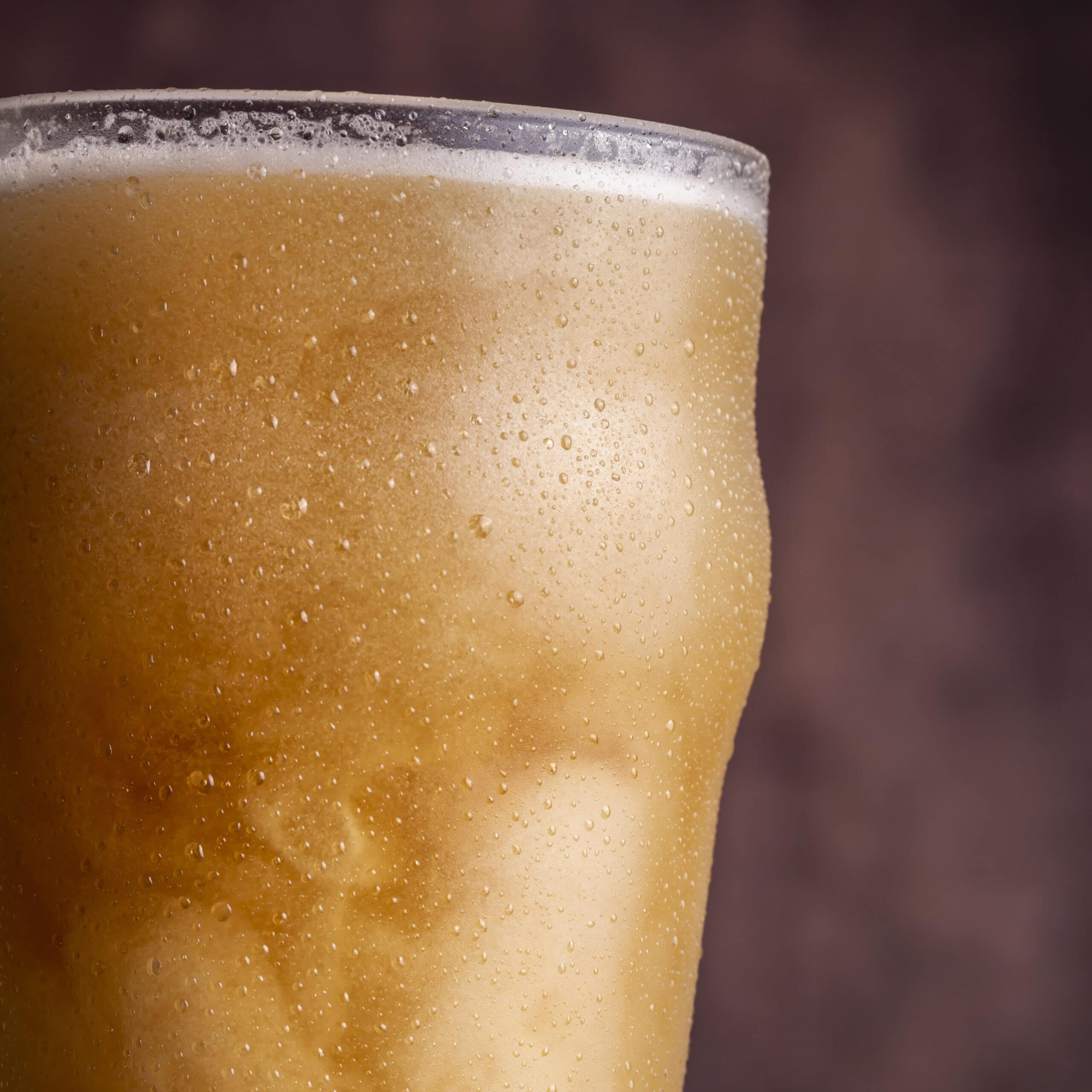 Detail of pint of cold unfiltered wheat beer with water droplets all over the glass