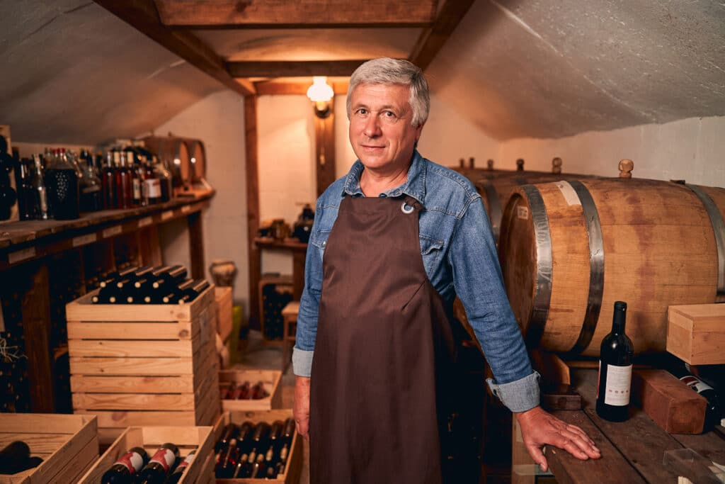 Smiling male winemaker standing in storage room with barrels and bottles of wine in wooden crates
