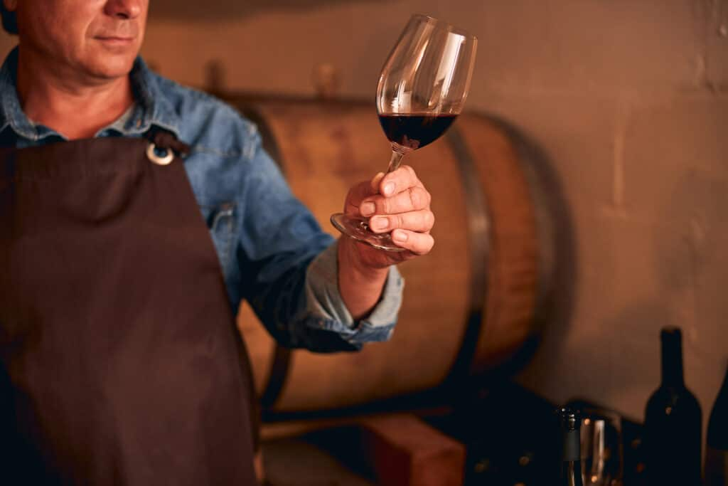 Close up of man in apron holding glass of alcoholic drink while standing in wine cellar