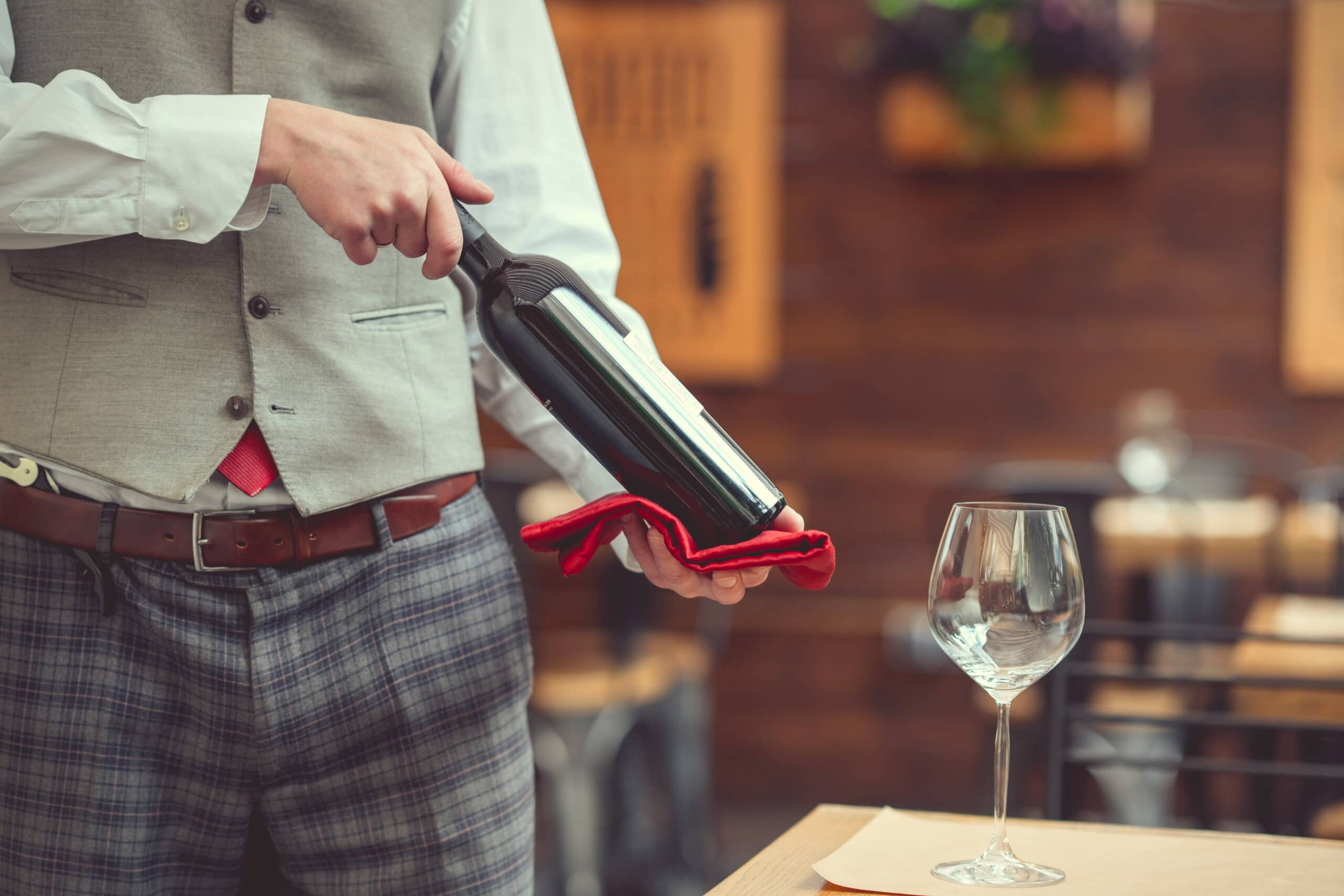 Young waiter with a bottle