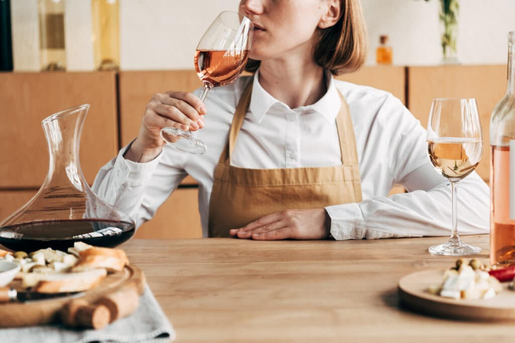 partial view of sommelier in apron sitting at table and tasting wine