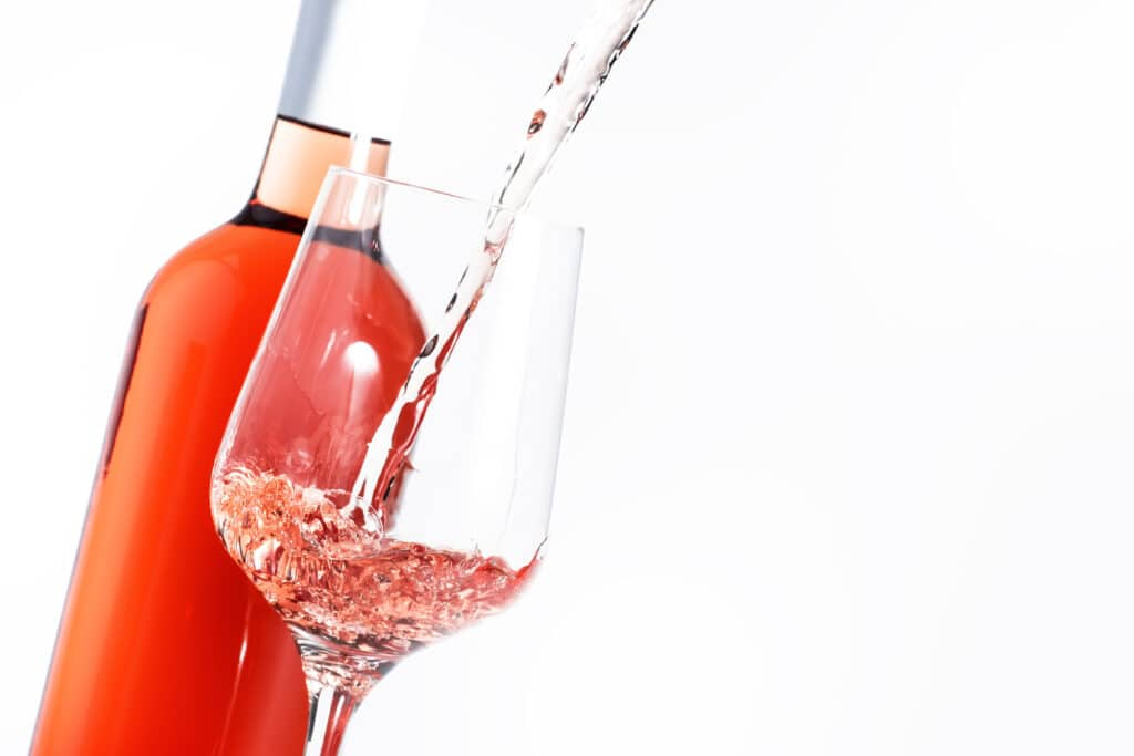 Rose wine pouring out of the bottle,