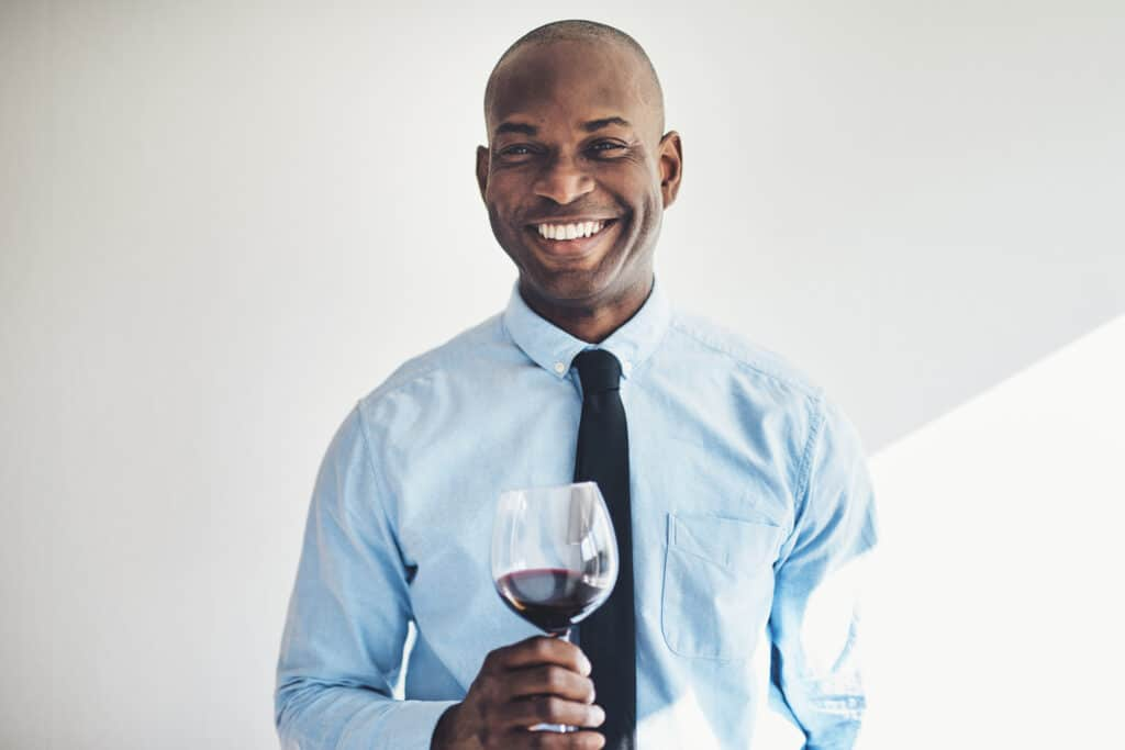 Smiling mature man drinking a glass of red wine