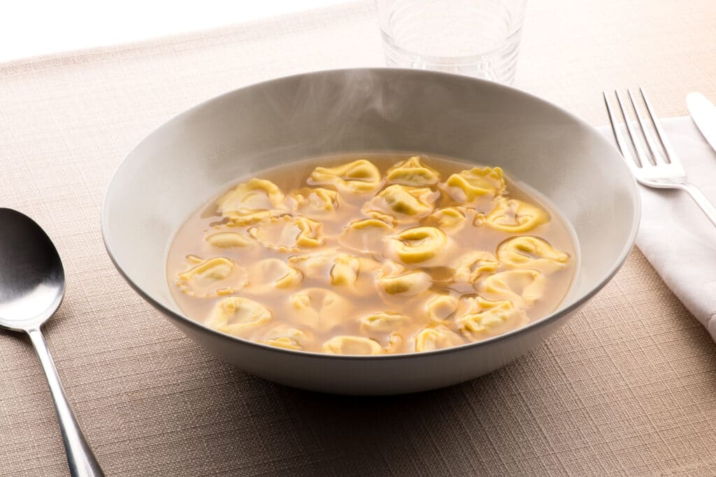 Tortellini al brodo, or tortellini pasta in savory broth, often chicken, from Emilia Romagna is a traditional first course for a holiday dinner such as Christmas