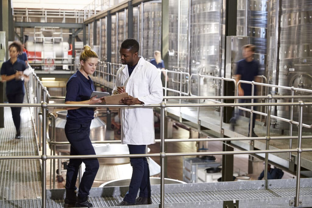 Two staff talking in a modern winemaking factory, close up