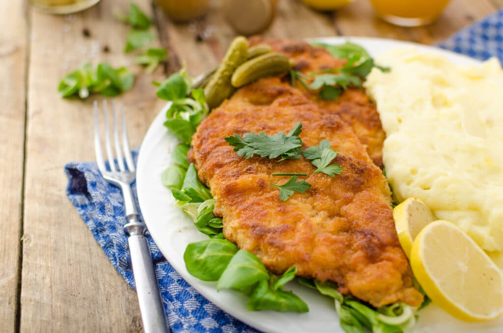 Wiener Schnitzel served with baked potatoes, pickled cucumbers and freshly squeezed orange juice