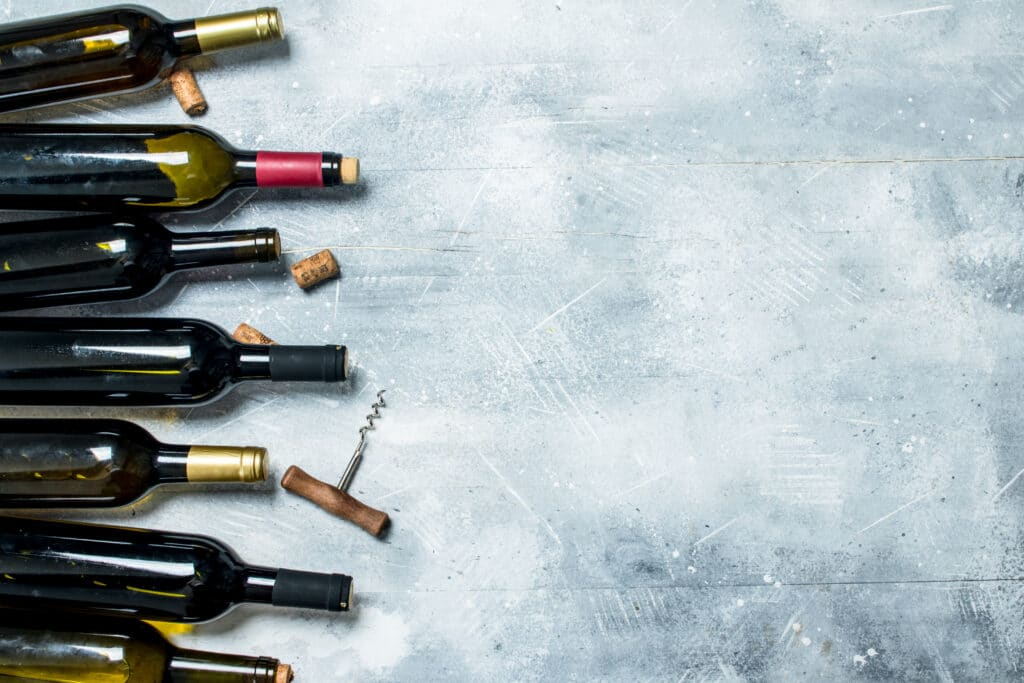 Wine background. Bottles of red and white wine. On a rustic background.