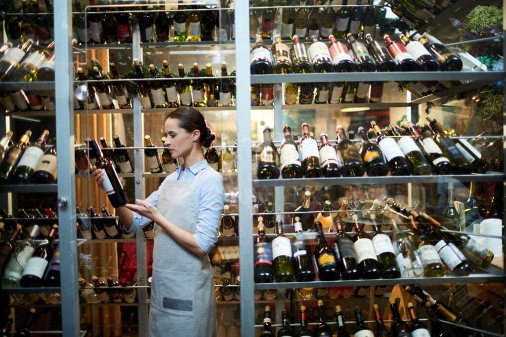 Waitress choosing a good wine from the wine cellar