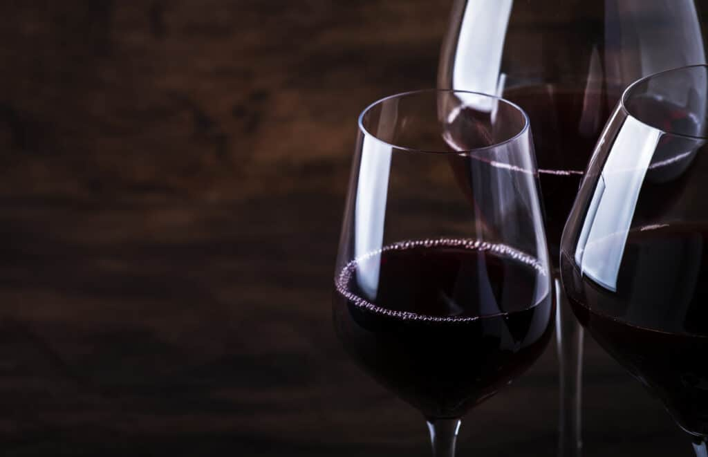 Wine glass. Selection of red wines on wine tasting. Dry, semi-dry, sweet red wine on old wooden table background. Copy space