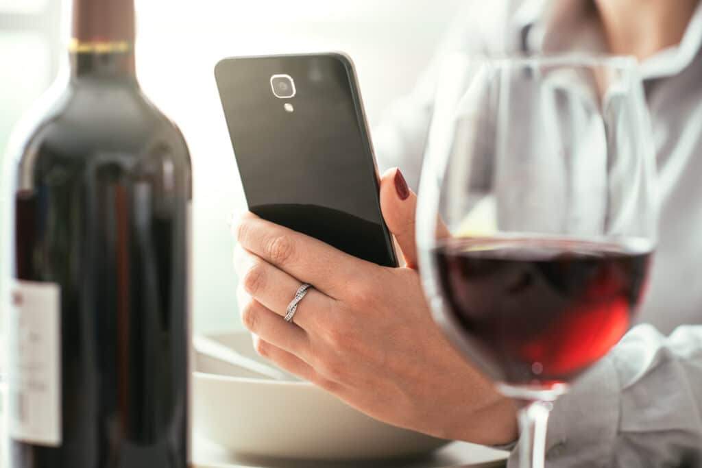 Woman using a wine app at the restaurant, she is scanning a wine label on a bottle, wine tasting and technology concept