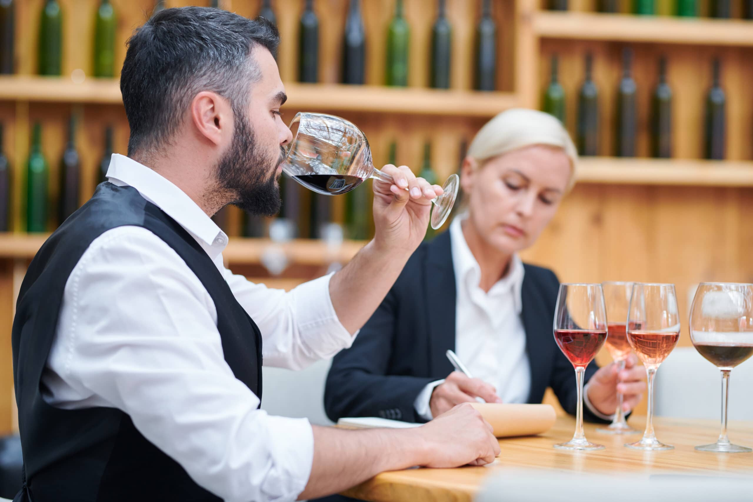Young elegant sommelier tasting red wine from one of glasses to check its quality and flavor
