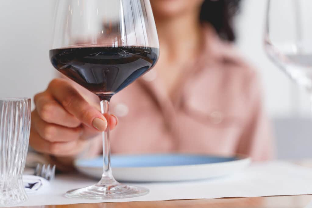 Close up of female hand holding glass of wine.